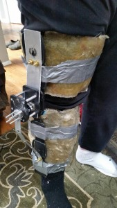 This is a photo of the user wearing the leg brace. The fiberglass works as a brace for their leg while the aluminum parts go down the leg and act as housing for the motors. They also acts as arms to drive movement of the leg as the motors turn.